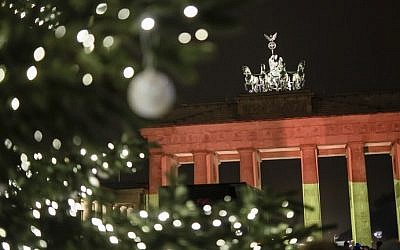 The Brandenburg Gate is seen in the colors of the German flag in Berlin on December 20, 2016 one day after a truck crashed into a Christmas market. (AFP Photo/Clemens Bilan)