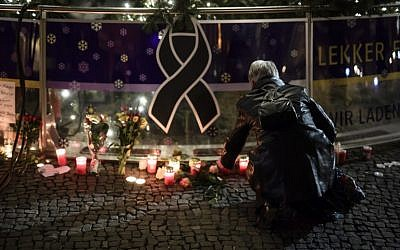 A woman lights a candle underneath the Christmas Tree near the Brandenburg Gate in Berlin on December 20, 2016 one day after a truck crashed into a Christmas market. (AFP/CLEMENS BILAN)