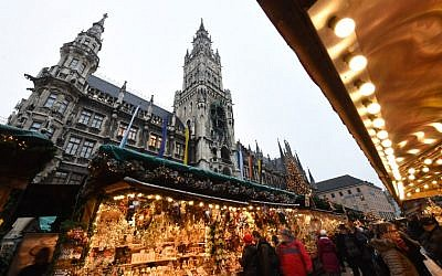 People walk between booths of the Christmas market in front of the city hall at the Marienplatz in Munich, southern Germany, on December 20, 2016, one day after a truck crashed into a Christmas market in Berlin.  (AFP PHOTO / Christof STACHE)