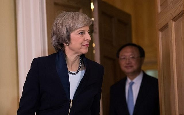 British Prime Minister Theresa May (L) enters the room followed by Chinese State Councillor Yang Jiechi (R) at the start of a meeting at 10 Downing Street in London on December 20, 2016.   (AFP PHOTO / POOL / Carl Court)