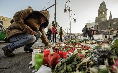 A mourner places a candle on December 21, 2016, at a makeshift memorial near the Kaiser Wilhelm Memorial Church in Berlin, close to the site where a truck crashed into a Christmas market two days before. (AFP Photo/Clemens Bilan)