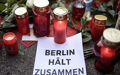 A paper reading in German 'Berlin sticks together' is pictured near the Kaiser Wilhelm Memorial Church in Berlin, close to the site where a truck crashed into a Christmas market two days before, on December 21, 2016 in Berlin. (AFP/Clemens Bilan)