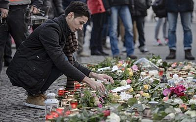 An Iraqi refugee lays a flower at a makeshift memorial near the Kaiser-Wilhelm-Gedaechtniskirche (Kaiser Wilhelm Memorial Church) in Berlin, close to the site where a truck crashed into a Christmas market two days before, on December 21, 2016 in Berlin. (AFP/Clemens Bilan)