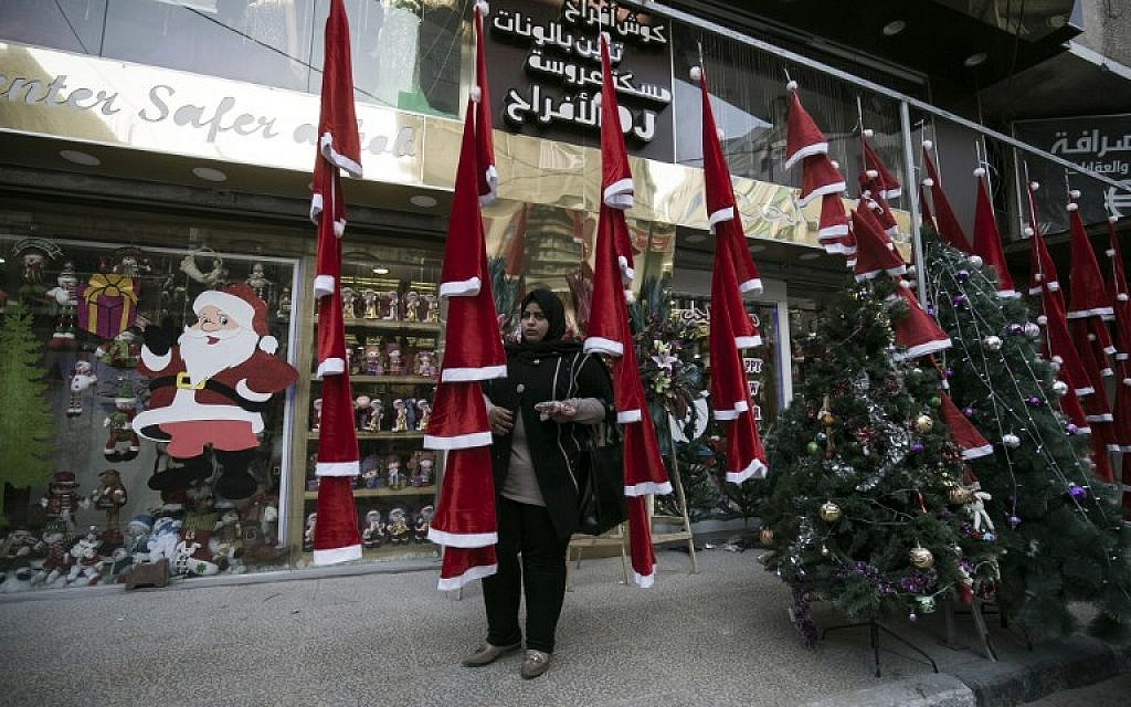A woman stands outside a shop selling Christmas ornaments and decorations in Gaza City on December 22, 2016. (AFP PHOTO/SAID KHATIB)
