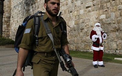 An Israeli soldier walks past a Palestinian man dressed up as Santa Claus outside Jaffa Gate in Jerusalem's Old City, on December 23, 2016. (AFP/Ahmad Gharabli)