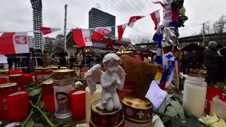 Candles, flowers and individual messages are placed at a makeshift memorial for the victims of the Christmas market attack near the Kaiser Wilhelm Memorial Church in Berlin on December 24, 2016. (AFP Photo/John Macdougall)