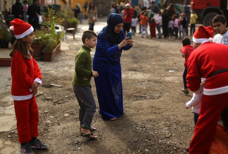 "A Syrian refugee from Aleppo takes a picture of her son posing with a Lebanese volunteer dressed as Santa Claus on December 24, 2016 during a gift distribution organized by the Maronite congregation ""Mission de Vie"" in a slum in the town of Dbayeh, north of Beirut. (AFP PHOTO / PATRICK BAZ)"