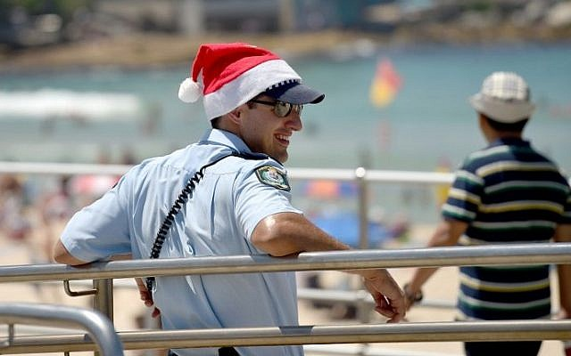 A policeman wearing a Christmas hat patrols Bondi Beach on Christmas Day in Sydney, Australia, on December 25, 2016. (AFP PHOTO / PETER PARKS)