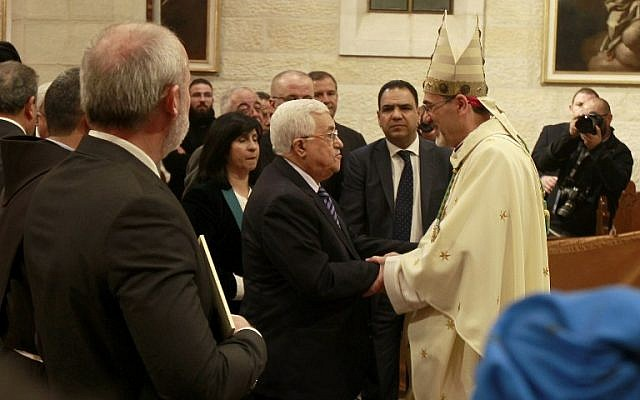 Palestinian Authority President  Mahmoud Abbas congratulates Archbishop Pierbattista Pizzaballa (R), apostolic administrator of the Latin Patriarch of Jerusalem, during the Christmas Midnight Mass in Saint Catherine's Church at the Church of the Nativity, on December 25, 2016 in Bethlehem, West Bank (AFP PHOTO AND POOL / MUSA AL SHAER)