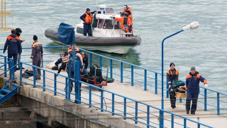 Russian rescuers carry a stretcher with passenger belongings after a Russian military plane crashed in the Black Sea, on a pier outside Sochi, on December 25, 2016. (AFP Photo/Stringer)
