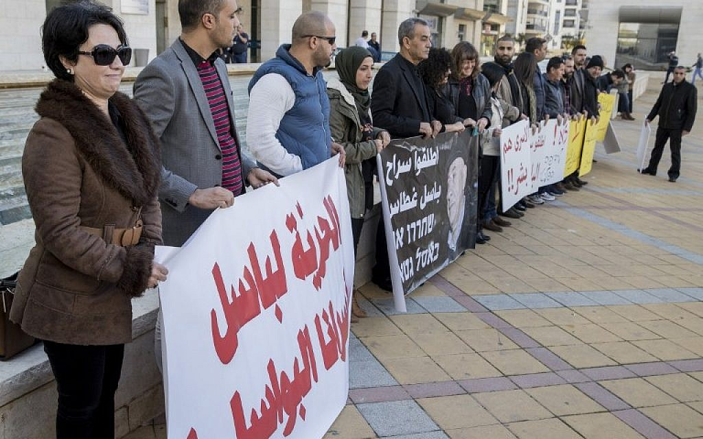 Protesters demonstrate outside Rishon Lezion Magistrate's Court as Arab MK Basel Ghattas attends a remand hearing, on December 26, 2016. (AFP PHOTO/JACK GUEZ)