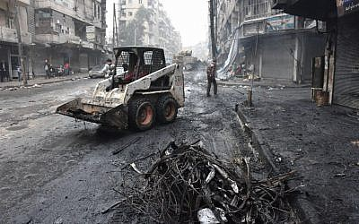 A tractor removes rubble as the Syrian government starts to clean up areas formerly held by opposition forces in the northern city of Aleppo on December 27, 2016, in the Shaar district. (AFP/George Ourfalian)