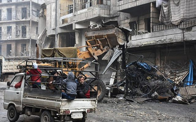 Syrian civilians drive past a tractor removing rubble as the Syrian government starts to clean up areas formerly held by opposition forces in the northern city of Aleppo on December 27, 2016, in the Shaar district. (AFP/George Ourfalian)