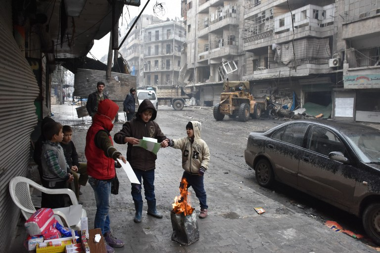 Syrian children gather around a fire as the Syrian government starts to clean up areas formerly held by opposition forces in the northern city of Aleppo on December 27, 2016, in the Shaar district. (AFP/George Ourfalian)