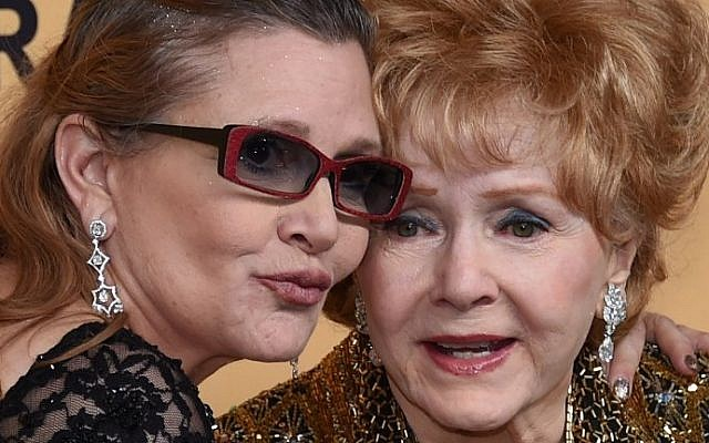 This file photo taken on January 24, 2015 shows Debbie Reynolds, right, recipient of the Screen Actors Guild Life Achievement Award, and her daughter Carrie Fisher posing in the press room during the 21st Annual Screen Actors Guild Awards at The Shrine Auditorium  in Los Angeles, California. (AFP/Getty Images North America/Ethan Miller)