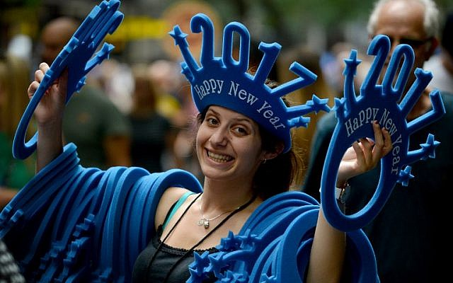 "A woman sells ""Happy New Year 2017"" headwear on a shopping street in Sydney, Australia on December 30, 2016. AFP PHOTO / Peter PARKS"