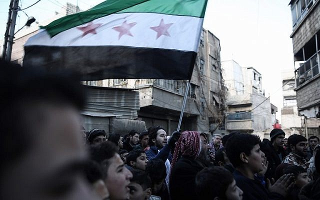 Syrian men gather in the rebel-held town of Saqba, on the eastern outskirts of the capital Damascus, during a demonstration against the Syrian regime, on December 30, 2016, on the first day of a nationwide truce. (AFP/Sameer Al-Doumy)