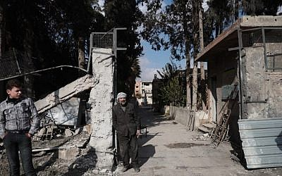 A Syrian boy and a school guard stand outside a school in the rebel-held town of Douma, on the eastern outskirts of Damascus, on December 30, 2016, on the first day of a nationwide truce. (Abd Doumany/AFP)