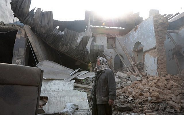 Syrian Abu Khaled stands amid the rubble of his destroyed house in the rebel-held town of Douma, on the eastern outskirts of Damascus, on December 30, 2016, on the first day of a nationwide truce. (AFP PHOTO/Abd Doumany)
