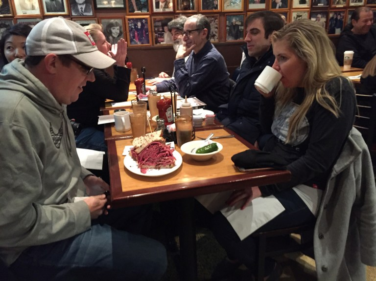 "New Yorker Paul Zatek (L) waits to take his first bite of a ""Woody Allen"" pastrami sandwich at the Carnegie Deli December 30, 2016 in New York. The deli will close after 79 years of service on December 30. (AFP PHOTO / Catherine Triomphe)"