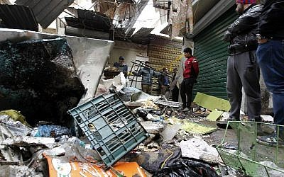 Iraqis look at the aftermath following a double blast in a busy market area in Baghdad's central al-Sinek neighborhood on December 31, 2016. (AFP/Sabah Arar)