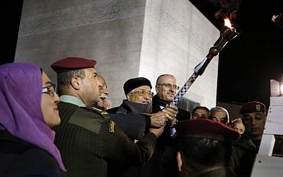 Palestinian Authority President Mahmoud Abbas (C) lights a flame to celebrate the 52 anniversary of the creation of the Fatah movement in the West Bank city of Ramallah on December 31, 2016. (AFP/Abbas Momani)