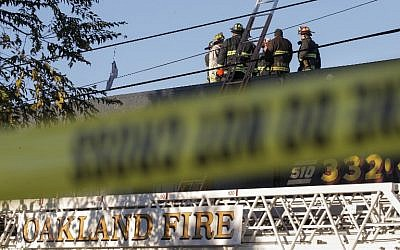 Firefighters investigate the scene of a overnight fire that claimed the lives of at least nine people during a warehouse party in the Fruitvale neighborhood on December 3, 2016 in Oakland, California. (Elijah Nouvelage/Getty Images/AFP)
