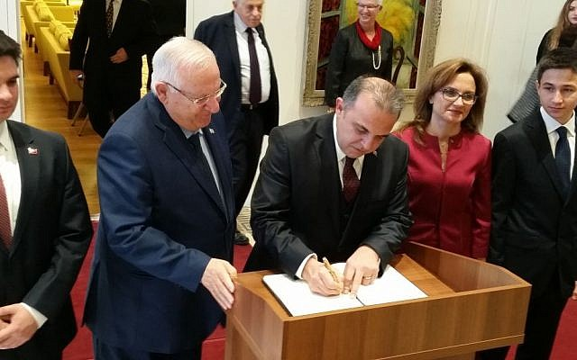 President Rivlin look on as Turkey's new ambassador to Israel writes into the President's Residence's guest book, December 12, 2016 (Raphael Ahren/TOI)