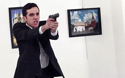 A man identified as Mevlut Mert Altintas holds up a gun after shooting Andrei Karlov, the Russian Ambassador to Turkey, at a photo gallery in Ankara, Turkey, December 19, 2016. (AP/Burhan Ozbilici)