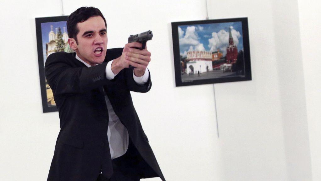 A man identified as Mevlut Mert Altintas holds up a gun after shooting Andrei Karlov, the Russian Ambassador to Turkey, at a photo gallery in Ankara, Turkey, December 19, 2016. (AP/Burhan Ozbilici)