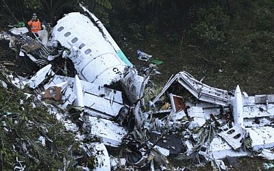 Rescue workers stand at the wreckage site of a chartered airplane that crashed in a mountainous area outside Medellin, Colombia, Tuesday, Nov. 29, 2016. The plane was carrying the Brazilian first division soccer club Chapecoense team that was on it's way for a Copa Sudamericana final match against Colombia's Atletico Nacional. (AP/Luis Benavides)