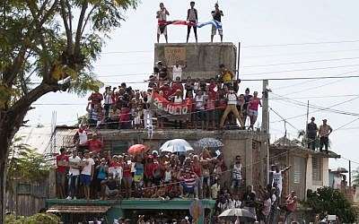 People stand on a building to get a better view of the funeral procession carrying the ashes of Fidel Castro, the last stage of the convoy arriving to Santiago, Cuba, Saturday, December 3, 2016. (Fernando Medina/Cubahora via AP)