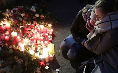 Two women mourn beside candles in Berlin, Germany, Tuesday, Dec. 20, 2016, the day after a truck ran into a crowded Christmas market nearby and killed several people. (AP Photo/Markus Schreiber)