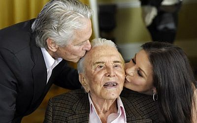 Actor Kirk Douglas, center, gets a kiss from his son Michael Douglas, left, and Michael's wife Catherine Zeta-Jones during his 100th birthday party at the Beverly Hills Hotel on Friday, Dec. 9. 2016, in Beverly Hills, Calif. (Chris Pizzello/Invision/AP)