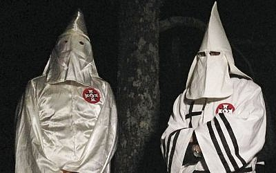 In this Friday, December 2, 2016 photo, two masked Ku Klux Klansmen stand on a muddy dirt road during an interview near Pelham, North Carolina. (AP Photo/Jay Reeves)