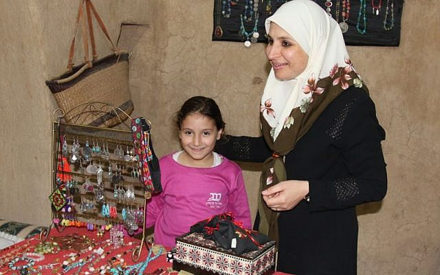 Amal Abu Karen with her daughter in front of some handicrafts produced by village artisans. (Shmuel Bar-Am)