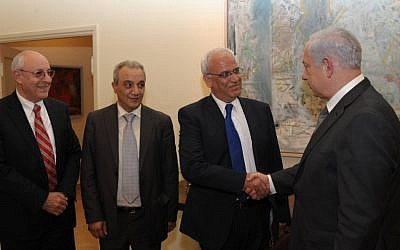 Prime Minister Benjamin Netanyahu shakes hands with Saeb Erekat in Jerusalem, April 2012. Netanyahu aide Yitzhak Molcho is at left, and PA security chief Majed Faraj is at second left. (Amos Ben Gershom/GPO/Flash90)