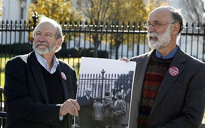 Michael, left, and Robert Meeropol, the sons of Ethel Rosenberg, pose next to an old photograph of them, before they attempt to deliver a letter to President Barack Obama in an effort to obtain an exoneration for their mother, in front of the White House, Thursday, Dec. 1, 2016. (AP Photo/Alex Brandon)