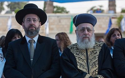 Chief Sephardi Rabbi Yitzhak Yosef, right, and Ashkenazi Chief Rabbi David Lau attend a New Year's ceremony of the Israel Police Command at the National Headquarters of the Israel Police in Jerusalem on September 7, 2015. (Yonatan Sindel/Flash90)