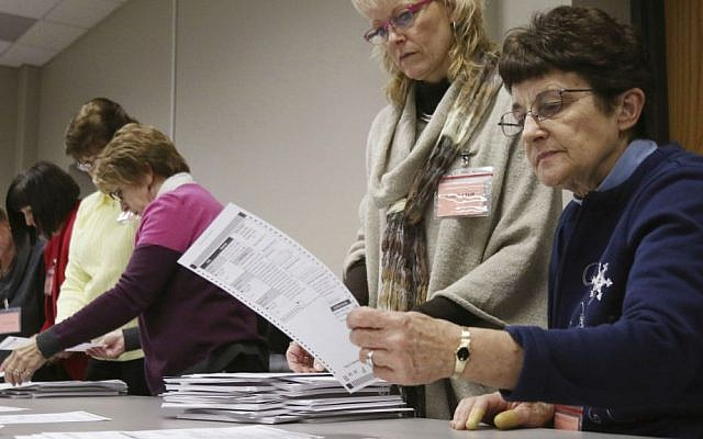 Tabulator Claudette Moll, right, from Farmington, looks over a ballot during a statewide presidential election recount Thursday, Dec. 1, 2016, West Bend, Wisconsin. (John Ehlke/West Bend Daily News via AP)