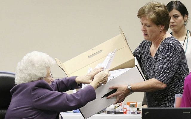 County Clerk Brenda Jaszewski holds a box of absentee ballots from the town of Erin, Wisconsin, as Board of Canvass member Marilyn Merten reaches to take a ballot out during a statewide presidential election recount, Thursday, Dec. 1, 2016, West Bend, Wisconsin. (John Ehlke/West Bend Daily News via AP)