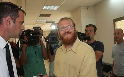 Rabbi Yosef Elizur (c) speaks with his lawyer in the Rishon Lezion court. August 2010 (Roni Schutzer/Flash90)