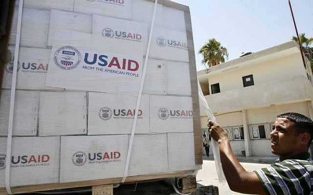 Illustrative: A Palestinian checks a truck loaded with humanitarian aid from the US as it arrives in the Palestinian town of Rafah through the Kerem Shalom crossing between Israel and the southern Gaza Strip on August 6, 2014. (Abed Rahim Khatib/Flash90)
