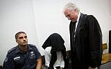 Ben Deri (c), accused of killing a 20-year old Palestinian man using live ammunition during clashes in Betunia in the West Bank, with lawyer Zion Amir (r), during his hearing at the District Court in Jerusalem on December 07, 2014. (Miriam Alster/Flash90)