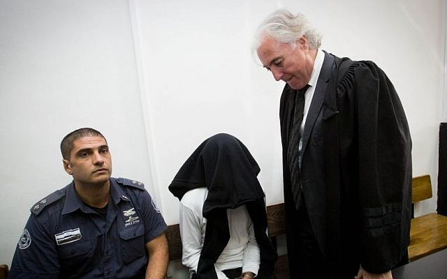 Ben Deri (c), accused of killing a 17-year old Palestinian using live ammunition during clashes in Beitunia in the West Bank, with lawyer Zion Amir (r), during his hearing at the District Court in Jerusalem on December 07, 2014. (Miriam Alster/Flash90)