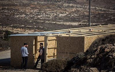 Young Israeli men build a structure in the West Bank outpost of Amona on November 28, 2016. The structure is meant to house supporters for when the state decides to evacuate the outpost, which was built on private Palestinian land. (Hadas Parush/Flash90)