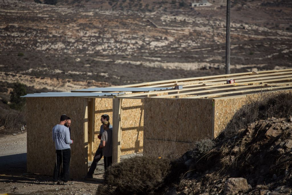 Young Jewish men seen building a structure in the Jewish settlement of Amona in the West Bank, on November 28, 2016. The structure is meant to house supporters for when the state decides to evacuate the illegal settlement. (Hadas Parush/Flash90)