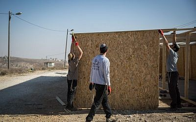 Young Jewish men seen building a structure in the Jewish settlement of Amona in the West Bank, on November 28, 2016. (Hadas Parush/Flash90)