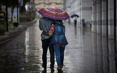 Illustrative: A couple walks with an umbrella in the rain in Tel Aviv, on December 1, 2016. (Nati Shohat/Flash90)