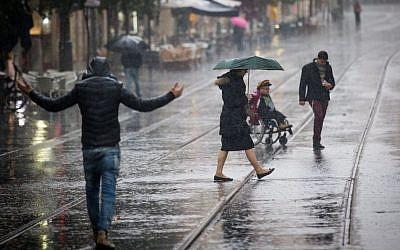 Illustrative: People walk in the rain on Jaffa Street in downtown Jerusalem on December 1, 2016. (Yonatan Sindel/Flash90)